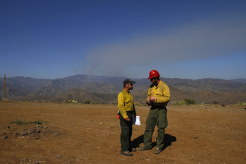 Two firefighters talk as smoke from the Gladiator Fire is visible in Cleator