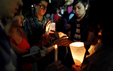Mexican citizens take part in a candlelight vigil on first anniversary of fire at a day care centre in Hermosillo, at the Angel of Independence Monument in Mexico City
