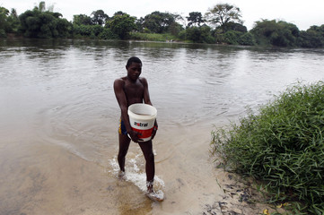 A man carries a bucket of sand from Lampassa river in Franceville