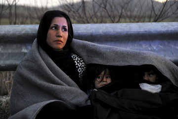 An Afghan mother covers herself and her children with a blanket while trying to reach the Greek-Macedonian border, following reports that Macedonia has closed its borders with Greece to Afghan migrants, near the village of Idomeni
