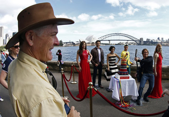 A man looks at wax figures of Australian celebrities placed for pictures in front of the Sydney Opera House and Harbour bridge