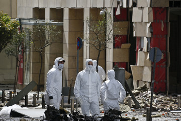 Forensic experts search for evidence on a street where a car bomb went off in Athens
