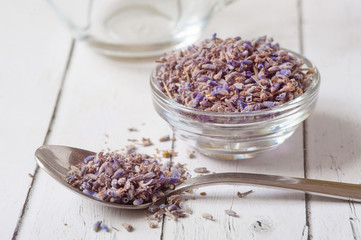 Lavender essential oil ingredients. Wooden spoon full of dry lavender seeds and bunch of dried...