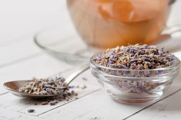 a cup of tea with fresh and dried lavender flowers on a white background. Natural herbal tea in a white porcelain cup garnished with fresh and dried herbs. Photo from above.