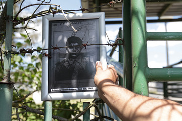 A participant of the European Meeting of Antiracist Leaders places a picture on a fence of a pig farm, situated at the site of a former Roma concentration camp, to commemorate victims of the Holocaust in Lety
