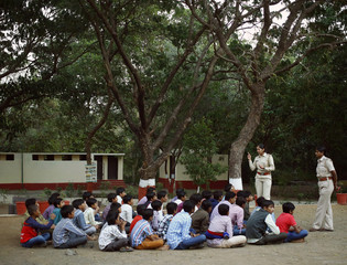 Forest guards speak with children during an awareness campaign on nature inside the premises of Gir National Park and Wildlife Sanctuary in Sasan