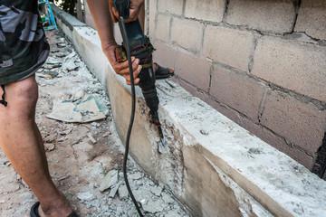 worker man drilling cement concrete floor with machine