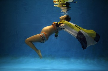 Jiejin Qiu, who is six months pregnant with her first baby, poses underwater during a photo shoot at a local wedding photo studio in Shanghai