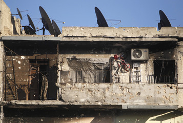 A bicycle hangs on a wall of a balcony of a damaged building in Aleppo's Karm al-Jabal district