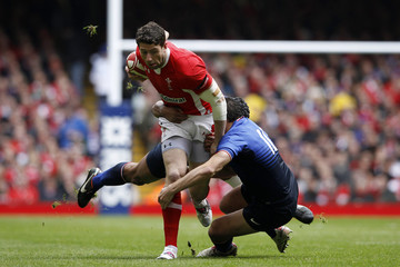 Wales' Cuthbert is tackled by France's Beauxis during their Six Nations rugby union match at the Millennium Stadium in Cardiff