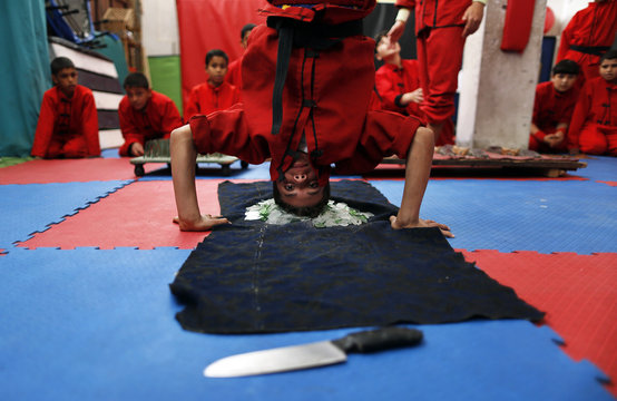 Palestinian boy stands on glass during a class at the Red Dragon martial arts club in Beit Lahiya
