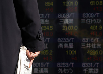 A man holding a newspaper looks at an electronic board showing stock prices outside a brokerage in Tokyo