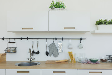 Bright kitchen background. The bright white kitchen. Wooden countertops, Interior view of elegant minimalist kitchen and dining area. No people.