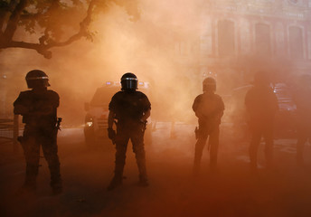 Riot police stand in red smoke during a protest by firemen against budgets cuts next to Catalunya's Parliament in Barcelona