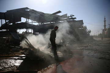 A man walks in a damaged site after a strike on the rebel held besieged city of Douma, in the eastern Damascus suburb of Ghouta