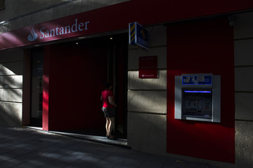 A woman enters a Santander bank branch in Madrid