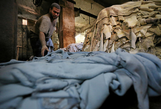 """A labourer works in a leather tannery where Co-founders of a local brand """"Okhtein"""", sisters Aya and Mounaz Abdelraouf, purchase leather in Cairo"""