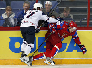 Team USA's Kristo collides into Russia's Biryukov as they fight for the puck during their 2013 IIHF Ice Hockey World Championship preliminary round match at the Hartwall Arena in Helsinki