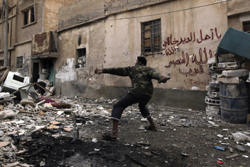 A Free Syrian Army fighter throws a homemade bomb towards forces loyal to Syria's President Bashar al-Assad in Deir al-Zor