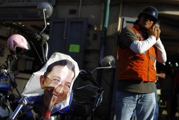 A man adjusts his helmet before riding his motorcycle, with a poster of Venezuelan President Hugo Chavez attached to it, outside a military hospital where he is being treated in Caracas