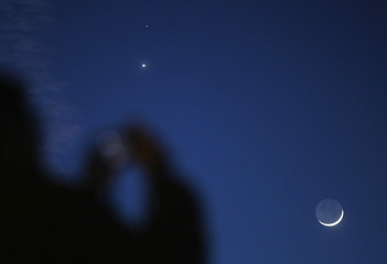 A man takes a picture of the crescent moon and planets Venus and Mars seen in the sky in central Bosnia