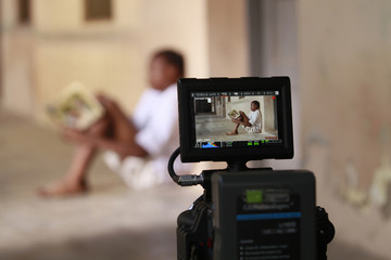 A boy is seen through a camera monitor as he acts in a scene during the making of 'Ake', in Abeokuta, southwest Nigeria