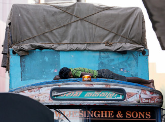 A man sleeps on top of a truck cabin parked along a road near a market in Colombo
