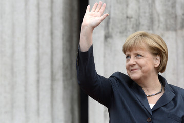 """German Chancellor Merkel waves to spectators  during the arrival for the """"Council of the Baltic Sea States"""" summit in Stralsund"""