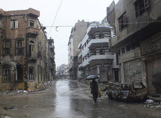 A man uses an umbrella as he walks along a damaged street in the besieged area of Homs