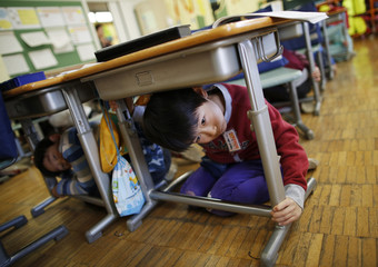 School children take shelter under desks during an earthquake simulation exercise at an elementary school in Tokyo