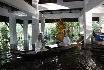 Buddhist nuns travel in a boat through floodwaters at the Sathira-Dhammasathan Buddhist meditation centre in Bangkok