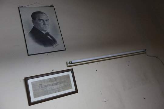 A copy of the first issue of Greek daily Apoyevmatini and a portrait of modern Turkey's founder Ataturk hang on the wall at the old office of Apoyevmatini in central Istanbul