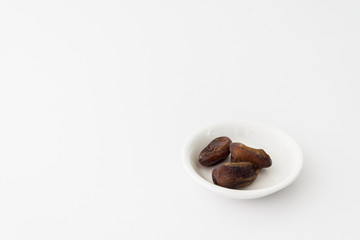 Dates or kurma in white plate over white background