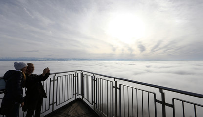 Two women take a picture of themselves as high fog covers the landscape around a look-out on Mount Uetliberg in Zurich