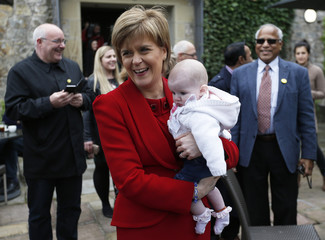 Nicola Sturgeon the leader of the Scottish National Party holds 5 month old baby Georgia Nicholl during a campaign visit in South Queensferry