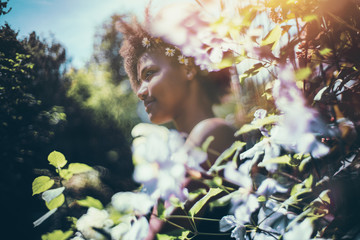 True tilt-shift view of young cute black female teenager with chamomile wreath on her head with curly afro hair, standing in beautiful summer garden surrounded by light pink and light blue flowers