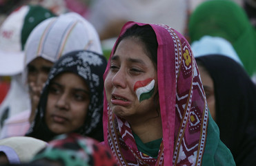 A supporter of Qadri cries next to fellow supporters during a speech by Qadri, in front of the Parliament House building during the Revolution March in Islamabad
