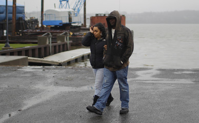A woman wipes tears from her face as she and a friend walk near the boat launch at the Hudson River in Newburgh