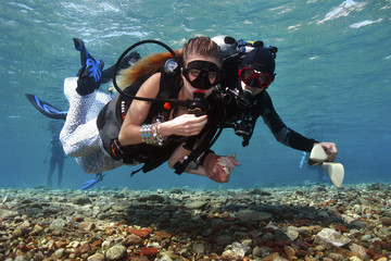 Assistant escorts a model as she dive to a location of an underwater photo shoot in the Red Sea in Eilat