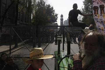 Farmers stand outside the Interior Ministry with their tractors and pictures of the 43 missing trainee teachers as riot police look on during a protest in Mexico City