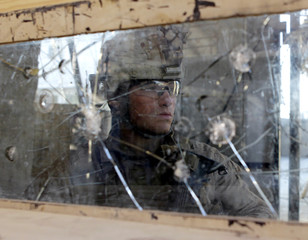 U.S. Marine Lance Corporal Kody Kuhlman of Fox Co, 2nd Battalion, 7th Marines Regiment stands guard behind a bullet-riddled windshield of an armoured vehicle at the guard post of Combat Outpost Musa Qal-Ah in Helmand province