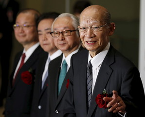 Japan Post Holdings Co Taizo Nishimuro, Japan Post Bank Co President Nagato and Japan Post Insurance Co President Ishii pose for photos during a ceremony to mark their company's debut on the Tokyo Stock Exchange in Tokyo