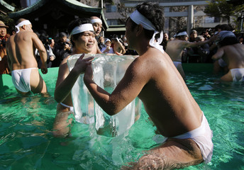 Men wearing a loin cloth hold onto ice as they bathe in ice-cold water at the Teppozu Inari shrine in Tokyo