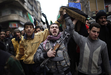 A Free Syrian Army fighter carries the body of his colleague Abdullah during his funeral in Aleppo