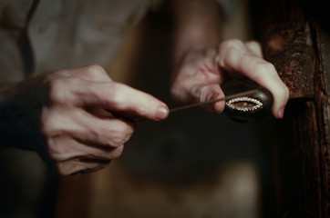 A man shapes a gold ring decorated with precious stones at a workshop in Karachi