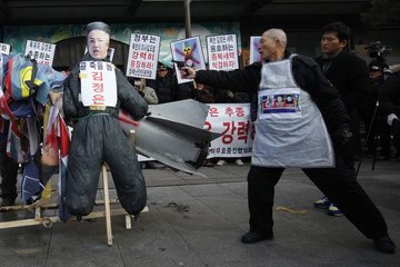 Anti-North Korean protester aims toy pistol at effigy of North Korean leader Kim Jong-Un during protest in central Seoul