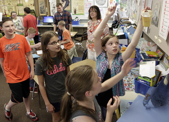 Sixth-grade student Hames tries out her group's design for a cup that drops a marble on a target via a zip-line as Boeing employees mentor students at after-school Science Technology Engineering and Math academy, in Covington, Washington
