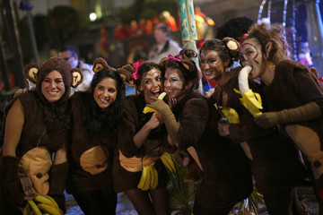 Women dressed up as monkeys pose for a photo before the New Year's celebrations in Coin