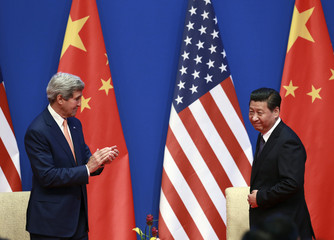 U.S. Secretary of State Kerry applauds as Chinese President Xi arrives on stage for the opening ceremony of the Sixth Round of U.S.-China Strategic and Economic Dialogue in Beijing