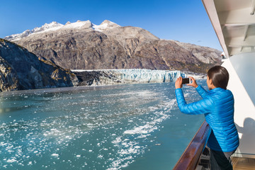 Wall Mural - Alaska cruise tourist taking photo of Glacier Bay. Ship passenger on balcony looking at view taking smartphone pictures of Margerie glacier from boat. Woman using phone app on travel vacation.